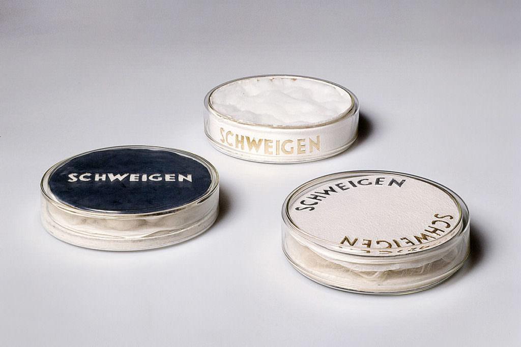 Runde glasschalen mit deckel mit weisser füllung und schrift