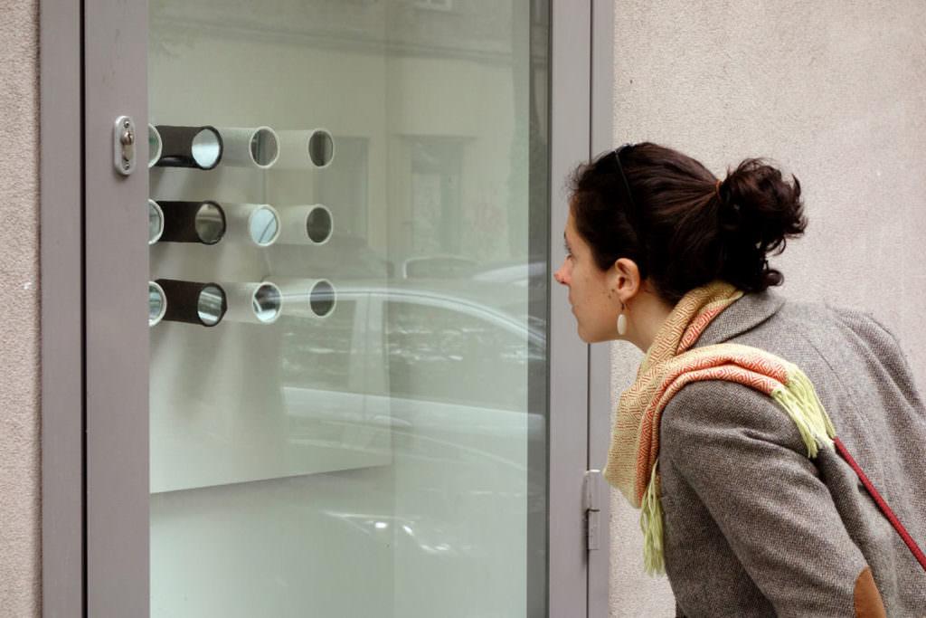 Frau blickt in Auslage mit Installation